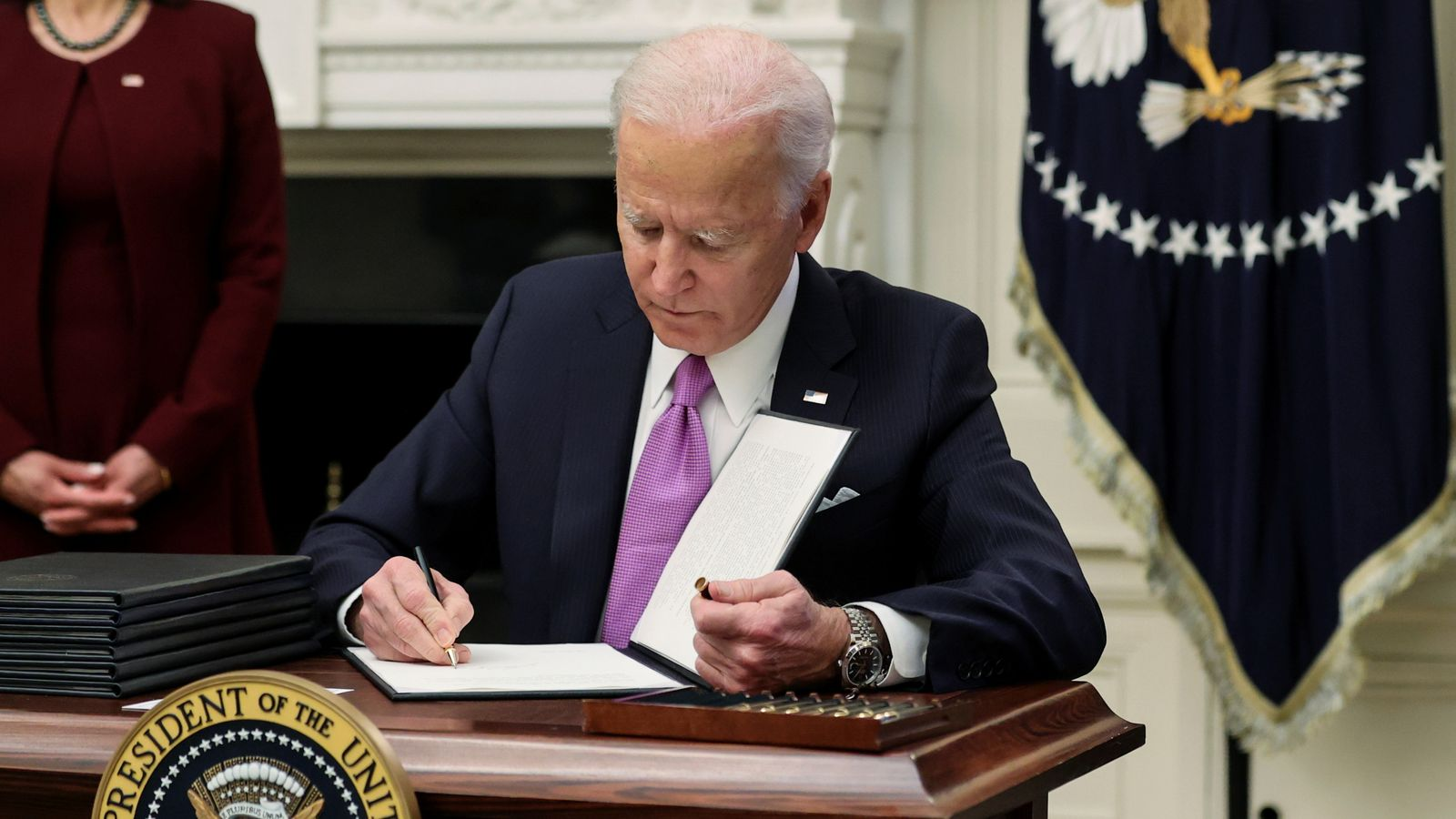 Joe Biden signs an executive order as part of his administration's plans to fight the coronavirus disease